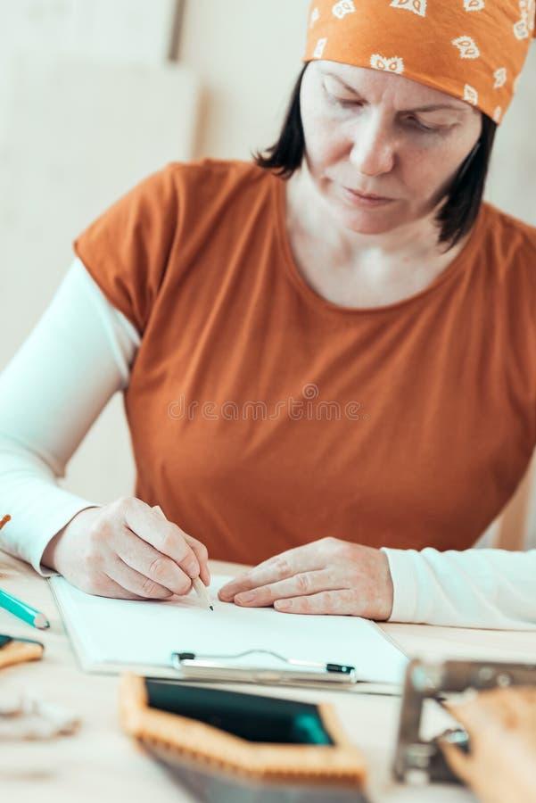Zelf - aangewende vrouwelijke timmerman het schrijven projectnota's stock afbeelding