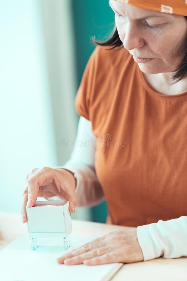 Zelf - de tewerkgestelde vrouwelijke timmerman stempelt projectdocumentatie stock foto