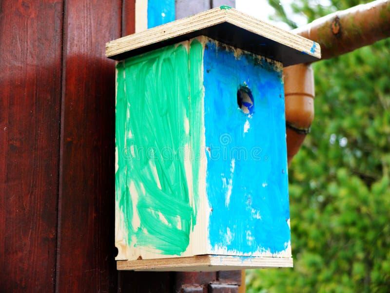 Zelf gemaakt die vogelhuis door een jong geitje in het groene en blauwe hangen op de houten muur wordt geschilderd Het concept vr stock afbeelding