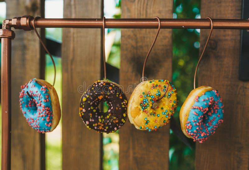 Zelf-gemaakte koekjes die op haken op omheining in de zomertuin hangen stock afbeelding