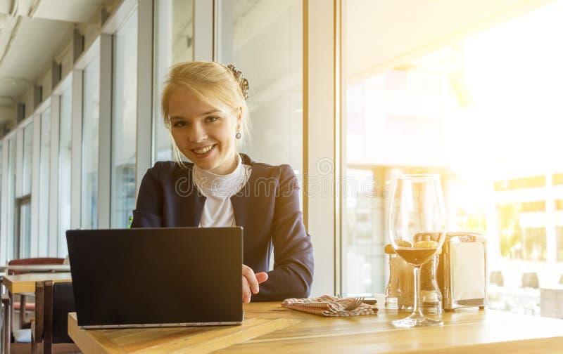 Zelf glimlachen - tewerkgestelde vrouw die aan project in modern coworking bureau werken stock foto