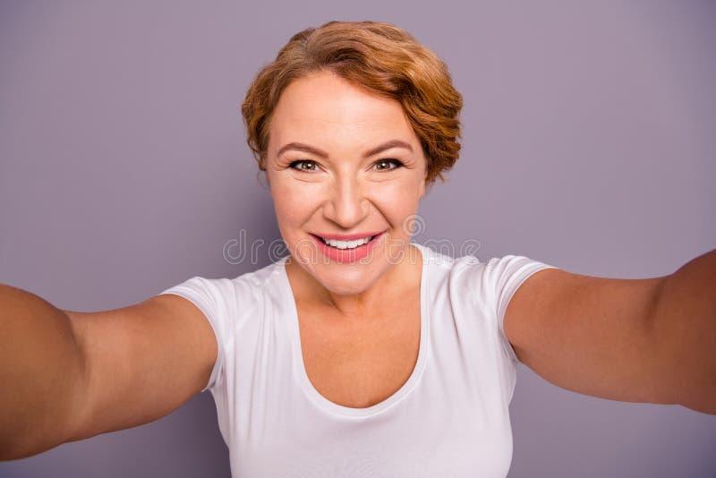 Zelf-portret van haar zij aardige aantrekkelijke aantrekkelijke vrolijke vrolijke wavy-haired geïsoleerde dame in toevallige witt stock foto