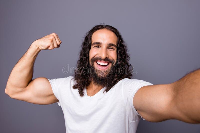 Zelf-portret van van hem toont hij aardige koele aantrekkelijke vrolijke vrolijke blije wavy-haired kerel die spier tonen trots a royalty-vrije stock foto