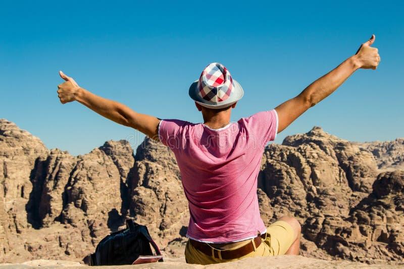 Zelf-tevreden mens in hoed op hoogste berg met omhoog duimen Geef motivatie geen concept op Gelukkige wandelaar die bereikend het stock fotografie