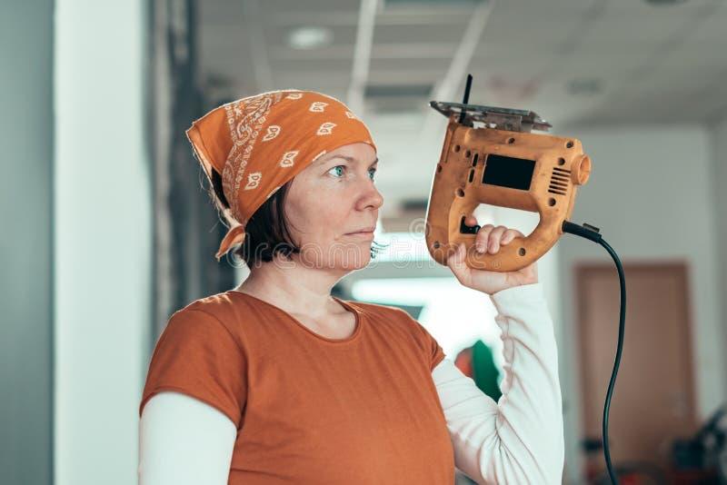 Zelf - tewerkgestelde vrouwelijke timmerman met elektrische figuurzaag stock foto's