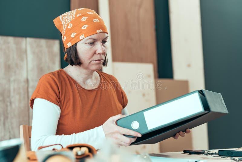 Zelf - tewerkgestelde vrouwelijke timmerman met het bindmiddel van de documentring royalty-vrije stock foto