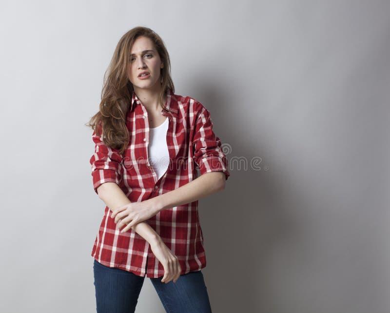 Zelf-verzekerde jonge vrouw met opgestroopte kokers royalty-vrije stock foto