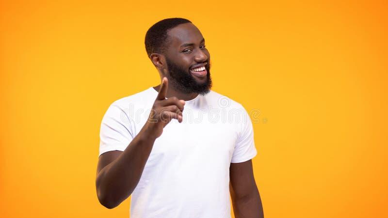 Zelfgenoegzame Afro-Amerikaanse mens die vingercamera richten en gele achtergrond glimlachen stock afbeelding