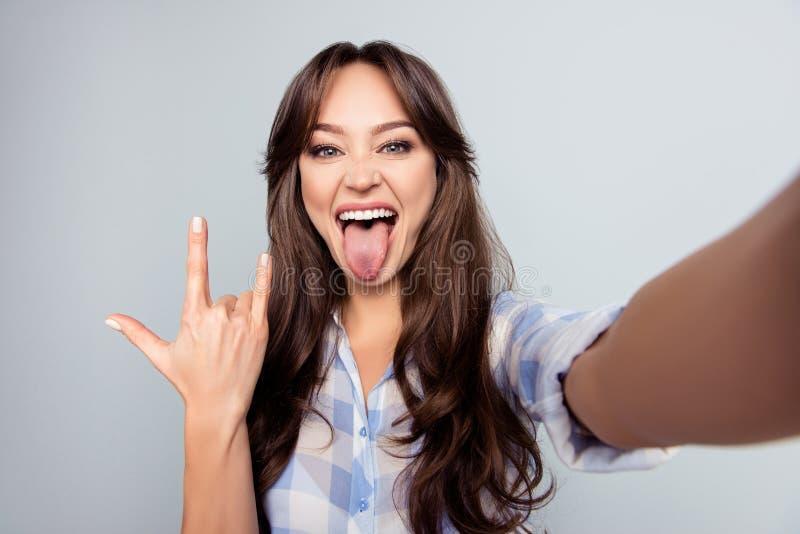 Zelfportret van aardige, aantrekkelijke, gekke vrouw, die selfie schieten stock foto's
