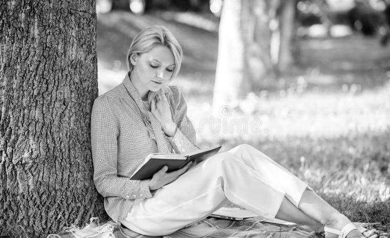 Zelfverbeteringsboek De bedrijfsdame vindt de minuut om boek te lezen haar kennis verbetert Meisjeshelling op boom terwijl binnen stock fotografie