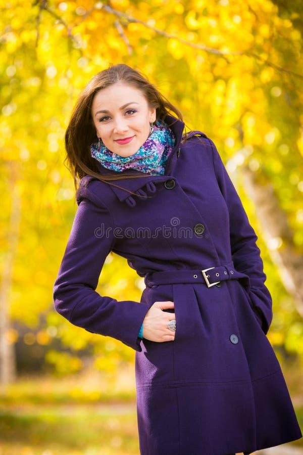 Zelfverzekerd meisje in donkerblauwe laag tegen de achtergrond van de herfstbladeren royalty-vrije stock foto's