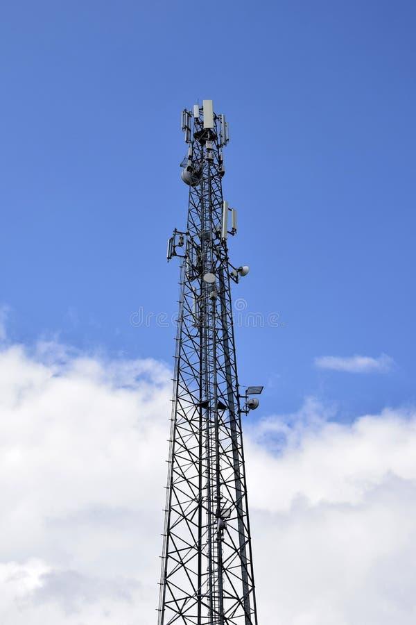 Zellturm gegen blauen Himmel mit Wolken Drahtlose Kommunikation stockfotografie