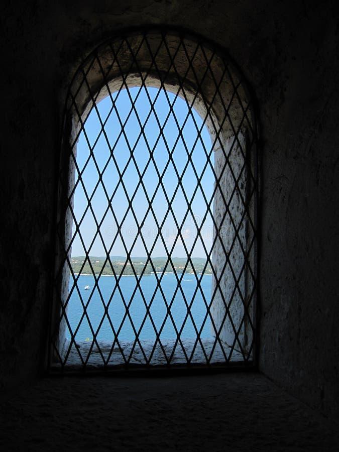 Zellwand mit einem Fenster mit Stangen mit Seeansicht, Innenperspektive stockbild