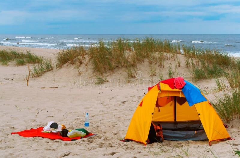 Zelt und Sachen auf dem Strand, touristisches Zeltgelb auf dem Sand lizenzfreie stockfotos