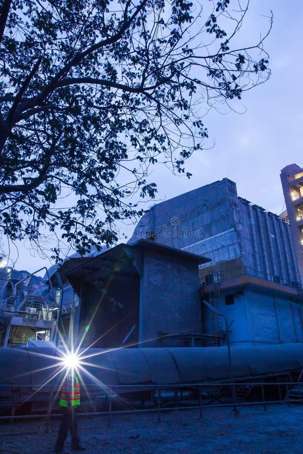 Zementfabrikfabrikherstellung an der D?mmerung, Funken der Arbeitskraft mit Scheinwerfertaschenlampe w?hrend der Arbeits?berstund lizenzfreie stockbilder
