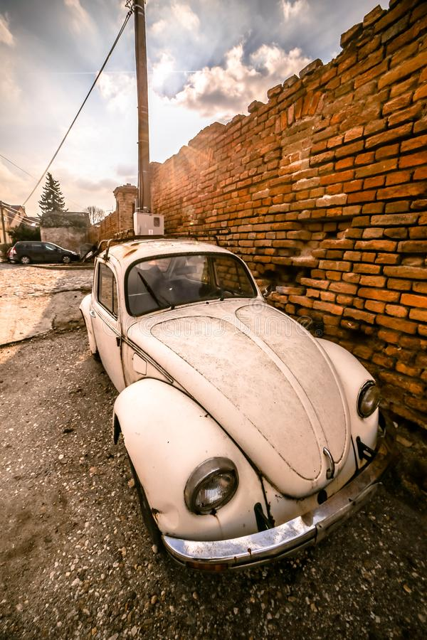 Zemun, Serbia - 17 February 2019 - Old rusted white Volkswagen Beetle parked next to orange brick wall.  stock photos
