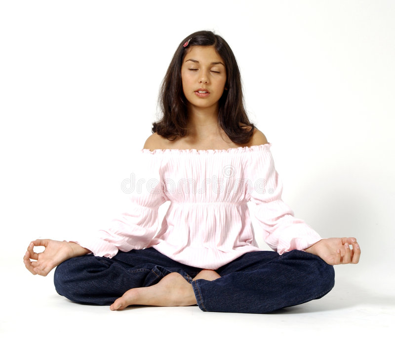 Zen. Young girl sitting crosslegged on a white backdrop. Girl is wearing a pink top and black jeans. Sitting with eyes closed at rest royalty free stock photo