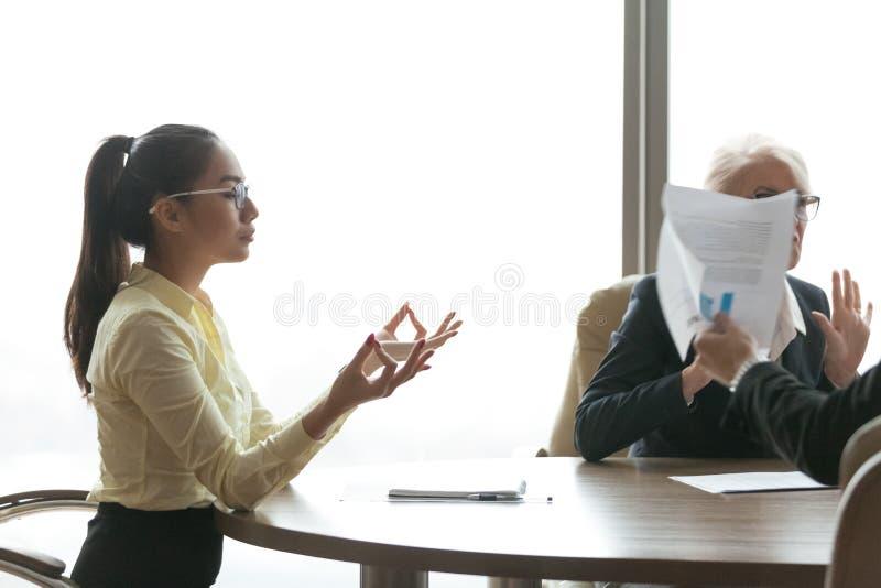 Zen asiático sereno de la sensación de la empresaria que medita durante la reunión agotadora imagen de archivo libre de regalías
