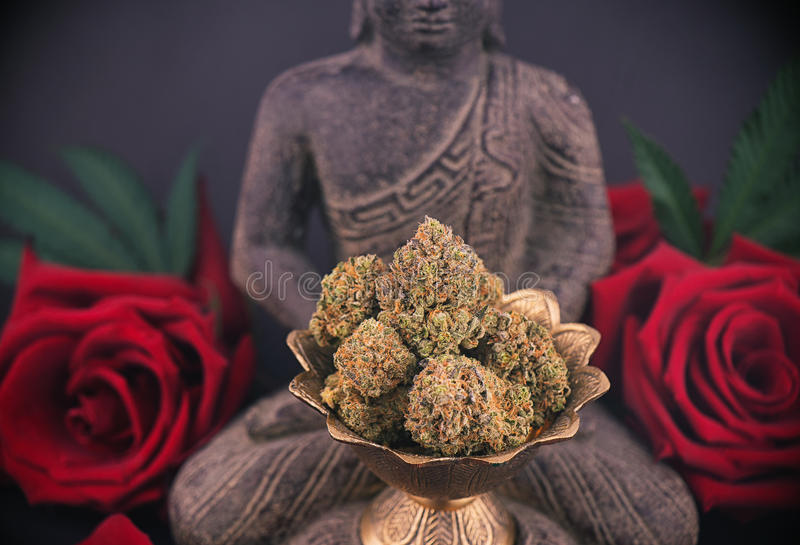 Zen background with roses and cannabis buds - medical marijuana. Zen smoky background with buddha statue, red roses and cannabis buds - medical marijuana and stock photos