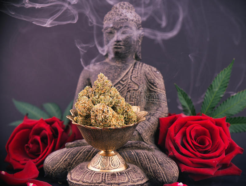 Zen background with roses and cannabis buds - medical marijuana. Zen smoky background with buddha statue, red roses and cannabis buds - medical marijuana and stock photo