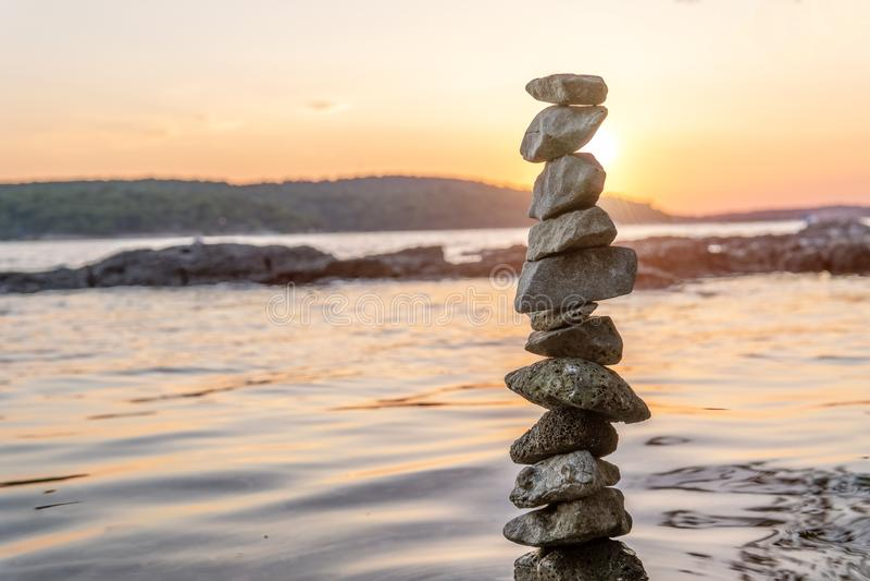 Zen balanserade stenar som staplas på havskust på solnedgången Jämvikts- och jämviktbegrepp arkivfoton