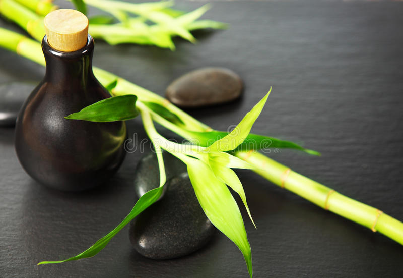 Zen basalt stones, bottle with massage oil and bamboo royalty free stock images