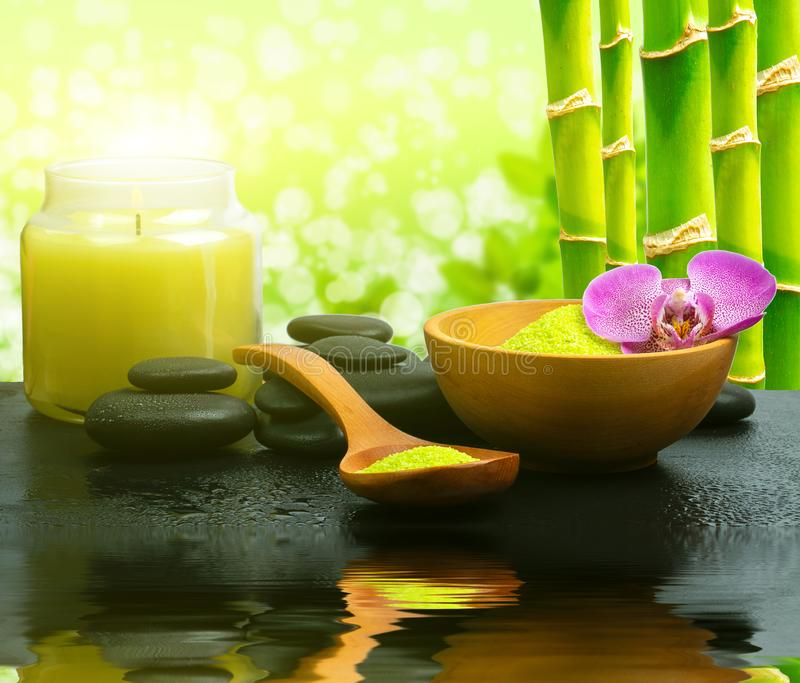 Zen basalt stones,candles, aromatic salt with green bamboo on water. Spa and Wellness concept. stock photo