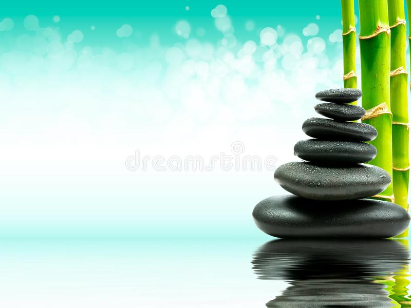 Zen basalt stones with green bamboo on water. Spa and Wellness concept. royalty free stock image