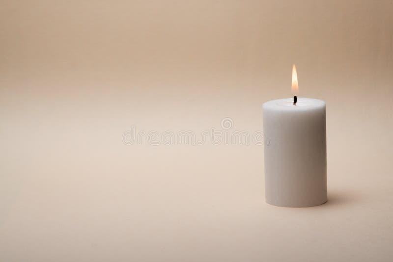 Zen come il concetto della stazione termale con soltanto una candela su fondo beige piacevole immagini stock
