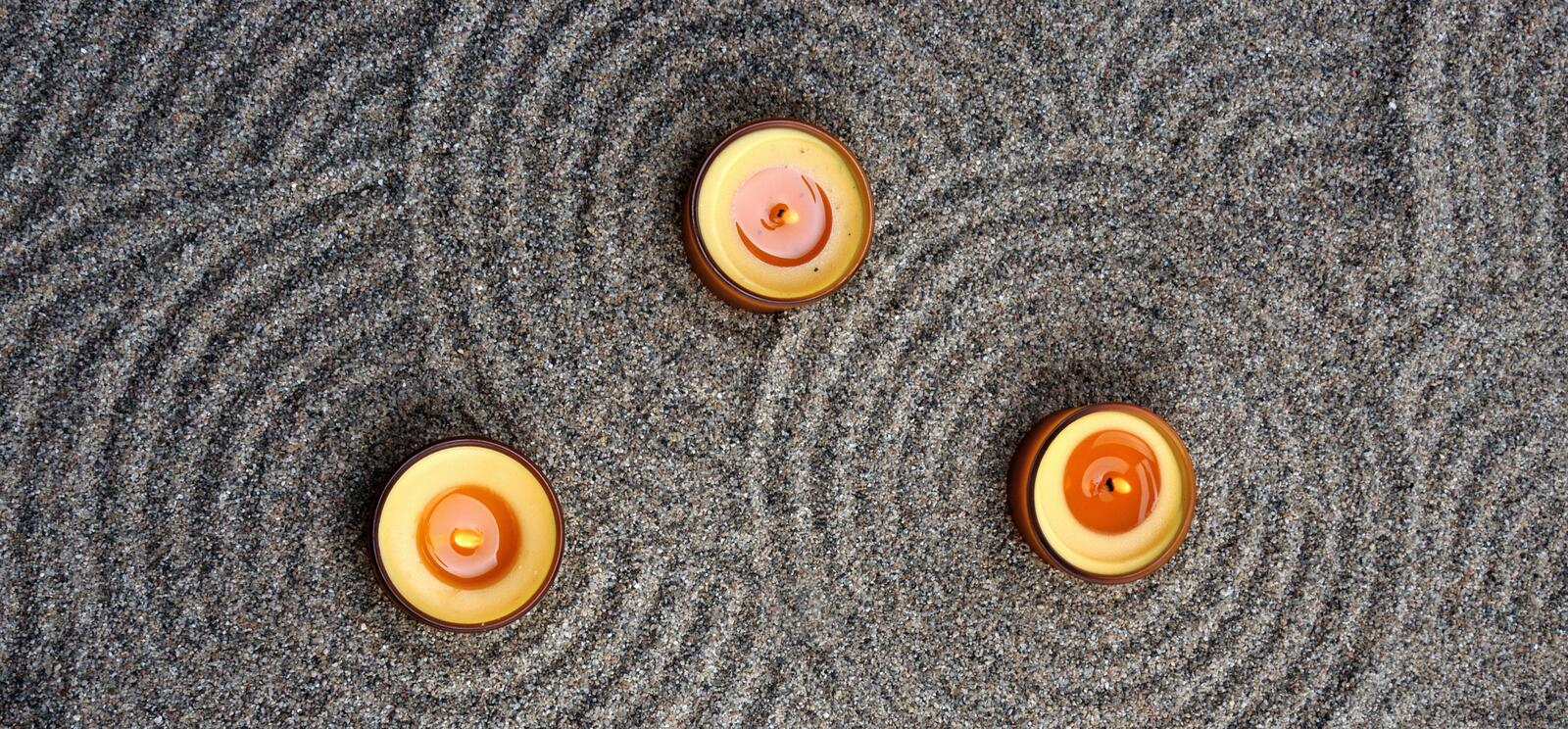 Candles in the sand. Calming patterns on the sand. royalty free stock images