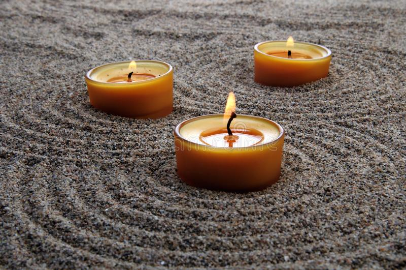 Candles in the sand. Calming patterns on the sand. stock photos
