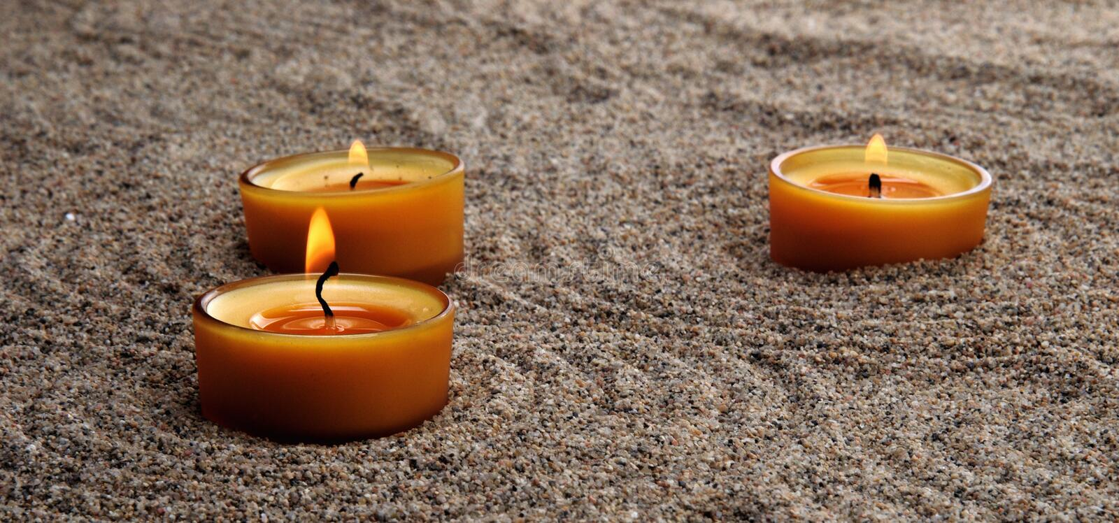 Candles in the sand. Calming patterns on the sand. stock images