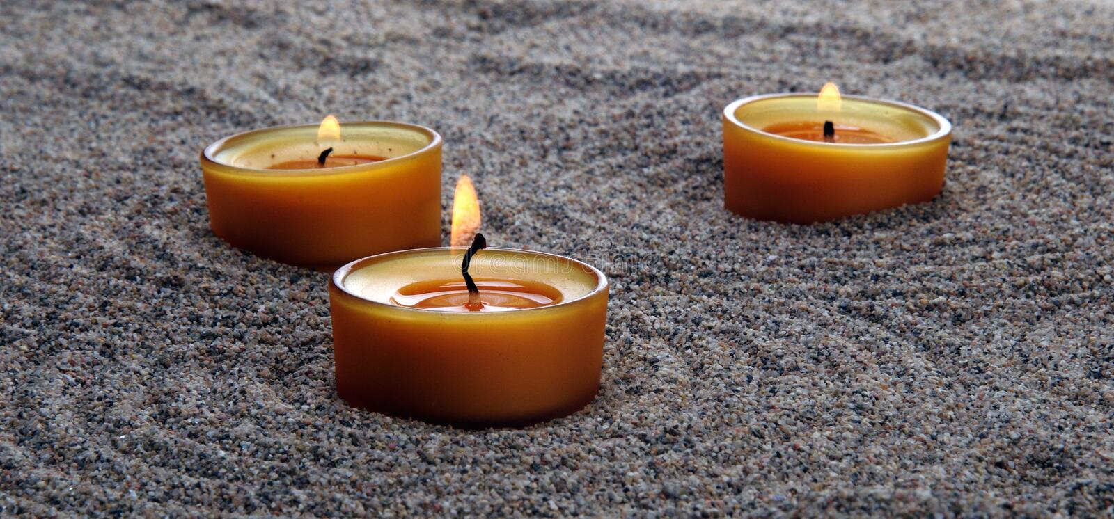 Candles in the sand. Calming patterns on the sand. stock photography