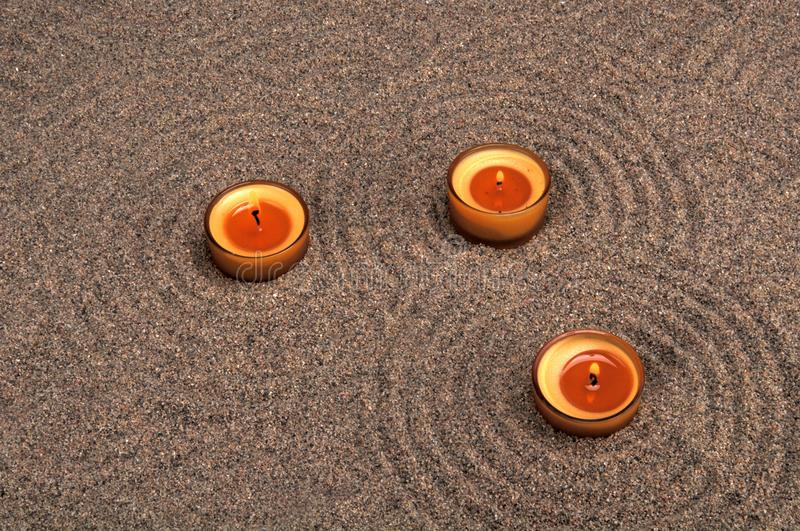 Zen composition. Candles in the sand. Calming patterns on the sand. royalty free stock photos