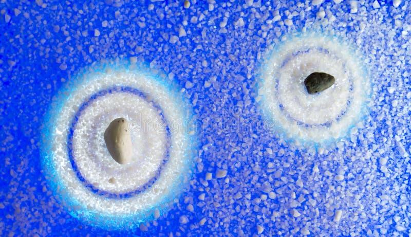 Zen del fondo da due pietre nei toni blu sul san originale immagini stock