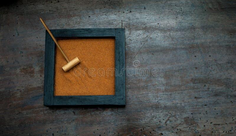 Zen garden with rake on orange sand. Zen garden base with rake and orange sand on aged scraped wood stock photo