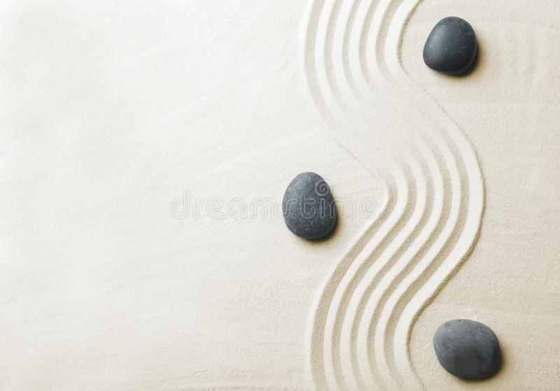 Zen garden stones on sand with pattern, top view. Space for text royalty free stock image