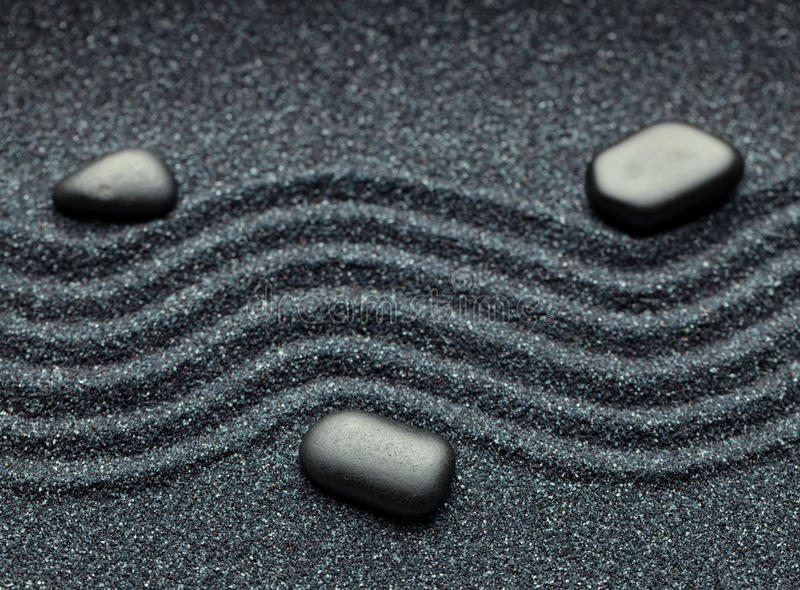 Zen garden with a wave lines in the sand with relaxing massage rocks stock image