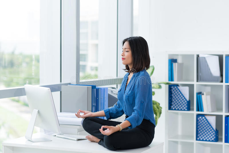Zen-like on table. Female office worker in lotus position sitting on table royalty free stock photography