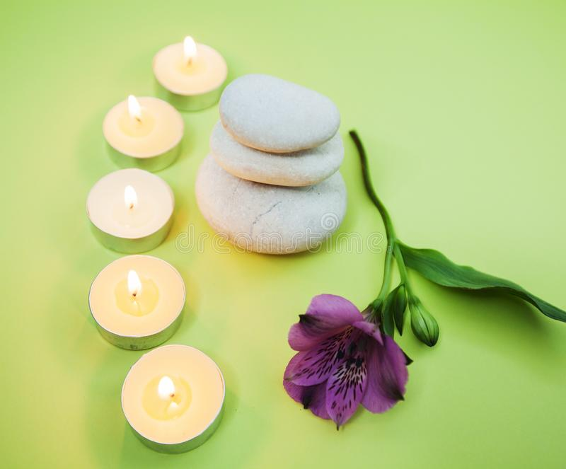 Zen Meditation Spa Lifestyle. Balanced stack of stones with aromatic candles and flower on green background stock photos