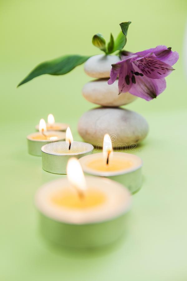 Zen Meditation Spa Lifestyle. Balanced stack of stones with aromatic candles and flower on green background stock photo