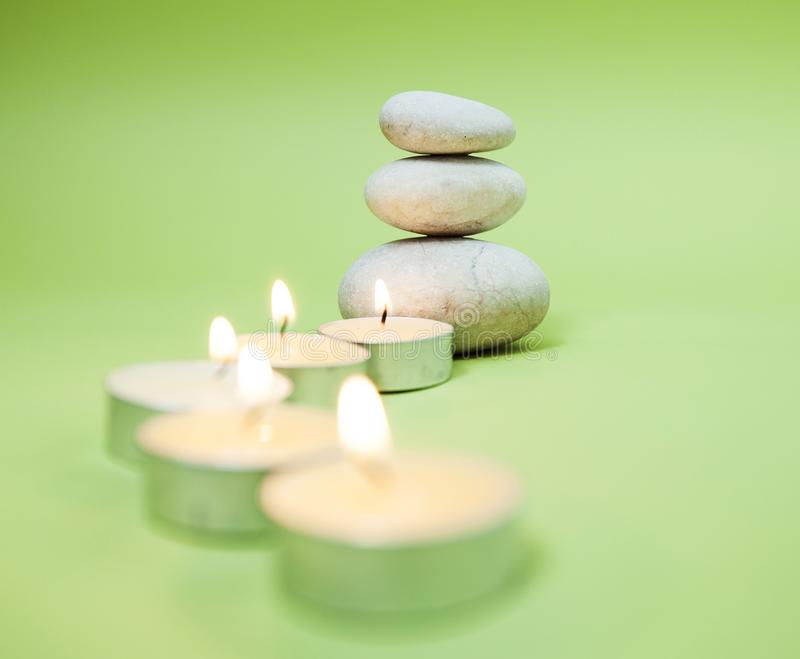 Zen Meditation Spa Lifestyle. Balanced stack of stones with aromatic candles on green background royalty free stock image