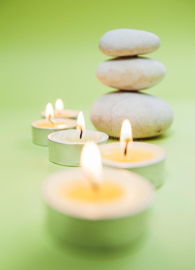Zen Meditation Spa Lifestyle. Balanced stack of stones with aromatic candles on green background royalty free stock photography