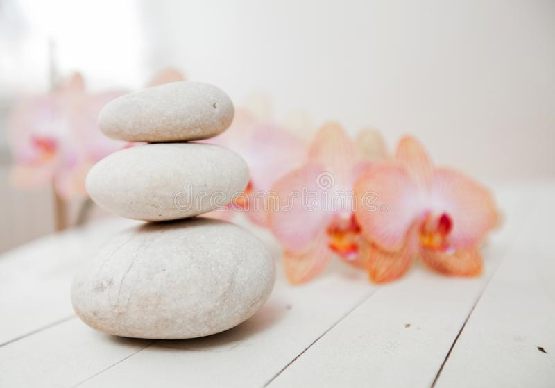 Zen Meditation Spa Lifestyle. Balanced stones and flower orchids on white wooden background royalty free stock photos