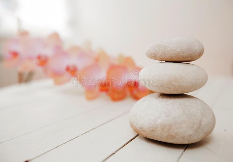 Zen Meditation Spa Lifestyle. Balanced stones and flower orchids on white wooden background stock images