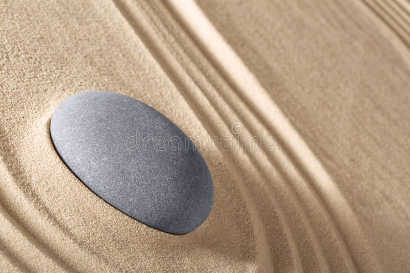 Zen meditation stone concentration and relaxation. Zen meditation stone traditional Japanese garden with sand and rock pattern concept for simplicity harmony and royalty free stock photography