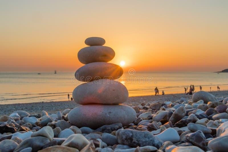 Zen Pebbles auf einem Strandsonnenuntergang lizenzfreies stockfoto