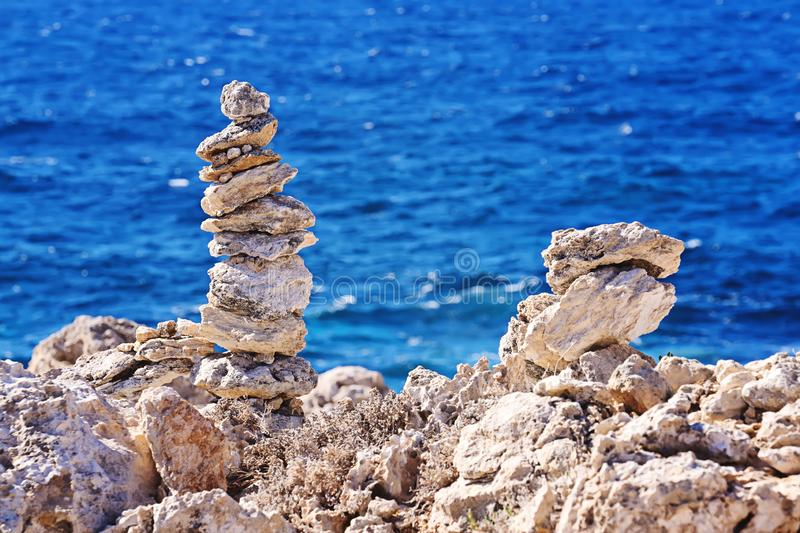 Zen pyramid of rough stones on the blurred sea background. Zen pyramid of stacked rough stones on the blurred sea background. Concept of balance and harmony royalty free stock photo
