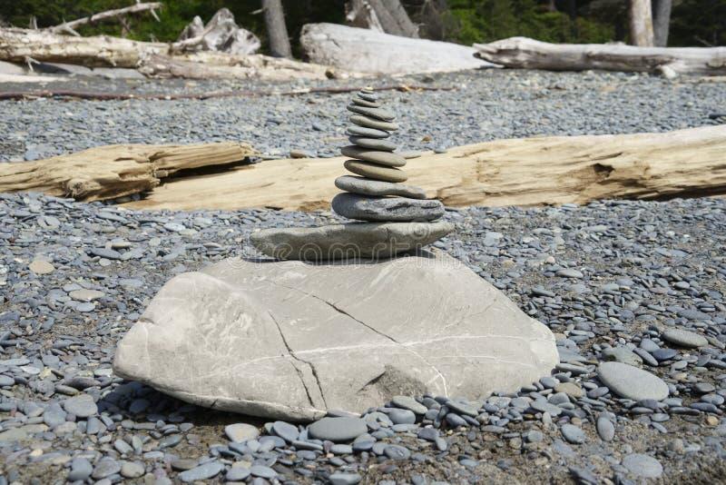 Zen rock på stranden med trä royaltyfri fotografi