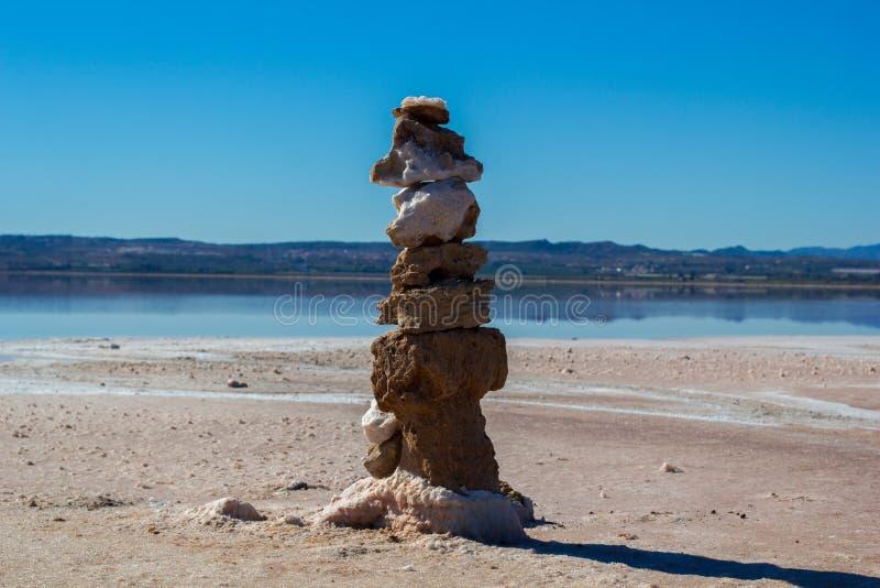 Zen salt-covered stone pyramids on salty lake background. Zen salt-covered stone pyramids on salty lake coast background, autumn in Spain, Torrevieja stock photos